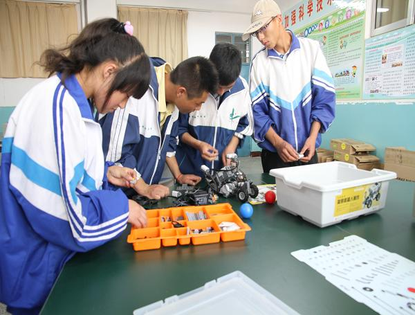 (科普活动室里四名中学生在认真的组装机器人)-银川科普网图片